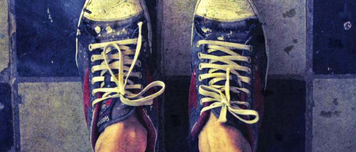 Tênis all-star azul calçado sem meia, provalmente com chulé