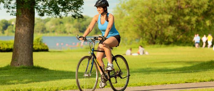 mulher pedalando bicicleta no parque